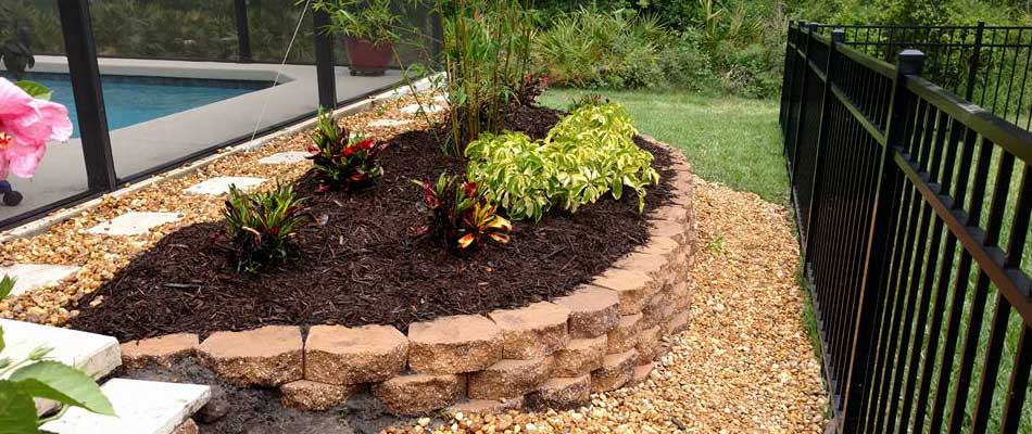 Raised landscape bed with retaining wall bricks in Parrish, FL.